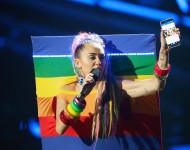 Host Miley Cyrus, styled by Simone Harouche, holding a Samsung phone