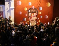 Members of the media and public gather by a mural of David Bowie in Brixton on January 11, 2016 in London, England. British music and fashion icon David Bowie died earlier today at the age of 69 after a battle with cancer.