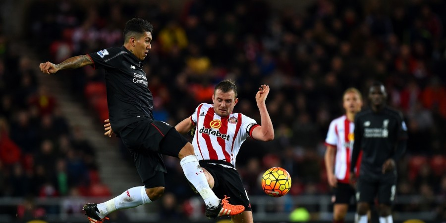 Roberto Firmino of Liverpool passes the ball under pressure from Lee Cattermole of Sunderland during the Barclays Premier League match between Sunderland and Liverpool at Stadium of Light on December 30, 2015 in Sunderland, England.