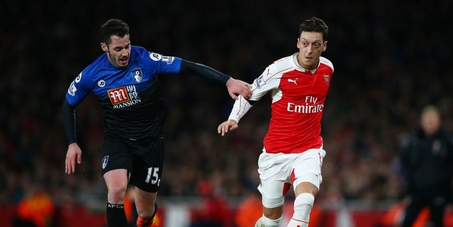 Mesut Ozil of Arsenal and Adam Smith of Bournemouth compete for the ball during the Barclays Premier League match between Arsenal and A.F.C. Bournemouth at Emirates Stadium on December 28, 2015 in London, England.