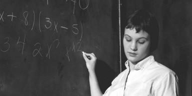 Solving a mathematics problem on a blackboard.