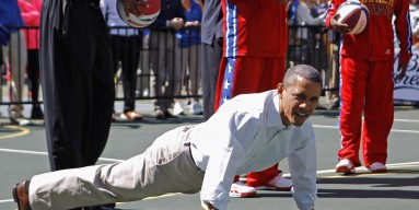President Barack Obama does pushups during the annual Easter Egg Roll on the White House tennis court April 9, 2012 in Washington, DC